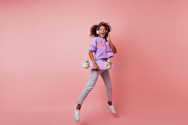 Full-length shot van prachtige zwarte vrouw in stijlvolle jeans springen op roze. krullend afrikaans meisje met skateboard positieve emoties uitdrukken.
