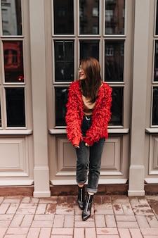 Full-length shot van stijlvolle vrouw in zwarte spijkerbroek en rood vest, leunend op wit venster in straat.