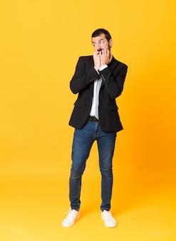 Full-length shot van zakenman nerveus en bang zijn handen naar de mond brengen
