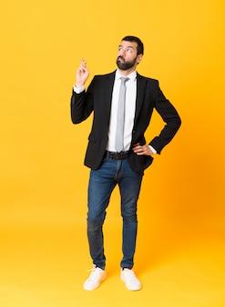 Full-length shot van zakenman over geel met vingers kruisen en wensen het beste
