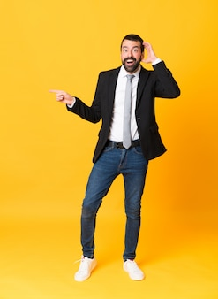 Full-length shot van zakenman over geel verrast en wijzende vinger naar de zijkant