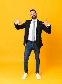Full-length shot van zakenman over geïsoleerde geel trots en zelfvoldaan