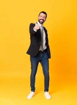 Full-length shot van zakenman over geïsoleerde gele muur met duimen omhoog omdat er iets goeds is gebeurd