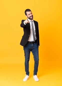 Full-length shot van zakenman over geïsoleerde gele punten vinger naar je met een zelfverzekerde uitdrukking