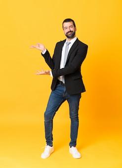 Full-length shot van zakenman over geïsoleerde gele uitbreiding van de handen aan de zijkant voor het uitnodigen om te komen