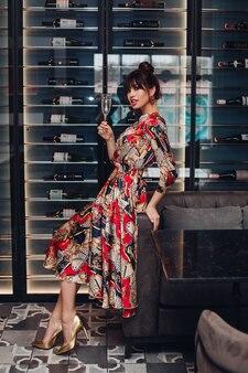 Full length stock photo portret van een prachtige dame die een luxe lange zijden jurk en gouden hoge hakken draagt. ze lacht met een glas champagne of wijn zittend op de bank in wijnmakerij of restaurant.