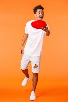 Full-length verticaal schot zorgeloze knappe afro-amerikaanse duizendjarige man die geniet van de zomer vrije tijd, buitenactiviteiten, gooien frisbee glimlachen en kijken naar vriend, oranje