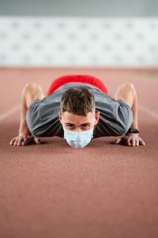 Full shot atleet doet push-ups met masker