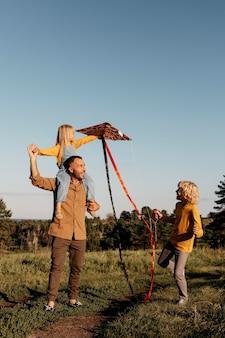 Full shot familie spelen met kite