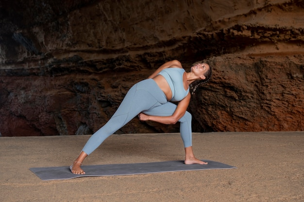 Full shot fit vrouw doet yoga pose buiten