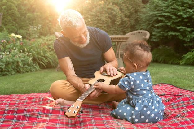 Full shot grootvader en kind met ukelele