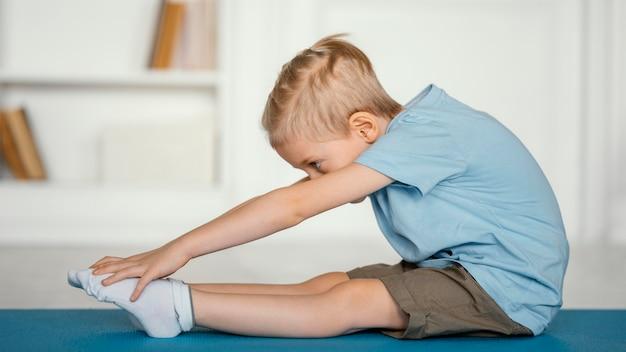 Full shot jongen die zich uitstrekt op yoga mat