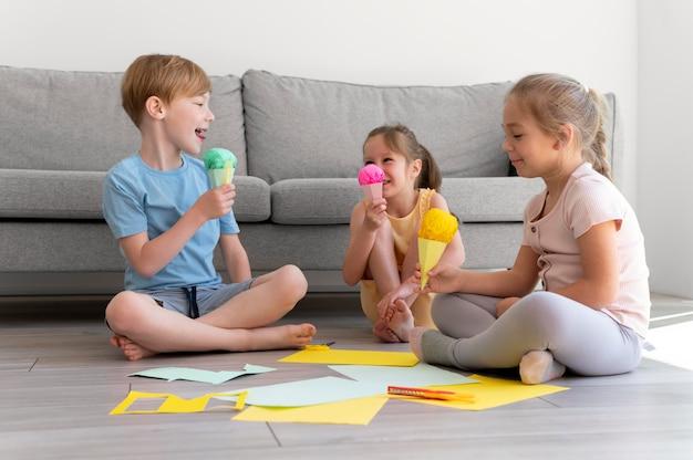 Full shot kids met papieren ijsjes