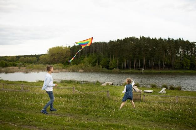 Full shot kinderen die buiten een vlieger vliegen