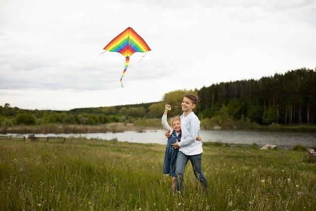 Full shot kinderen die een vlieger vliegen