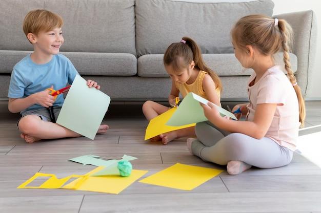 Full shot kinderen die met papier werken