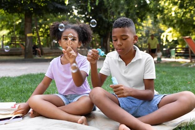 Full shot kinderen die zeepbellen maken