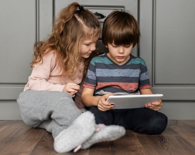 Full shot kinderen kijken naar tablet
