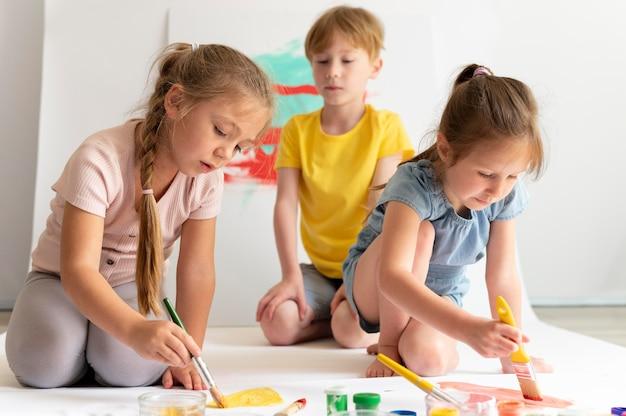 Full shot kinderen schilderen op hetzelfde papier