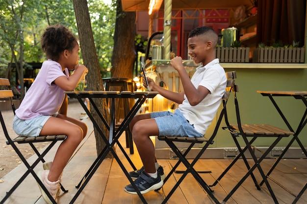 Full shot kinderen zitten aan tafel met tablet