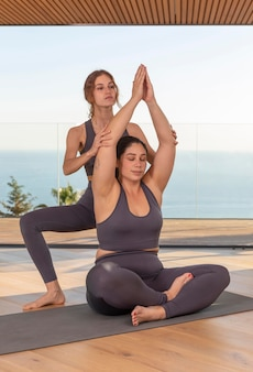 Full shot leraar helpen vrouw met pose