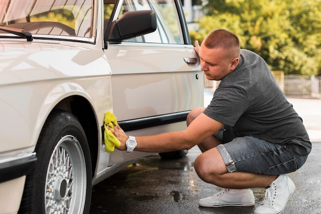 Full shot man auto met een doek schoonmaken
