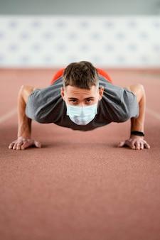 Full shot man doet pushups met masker
