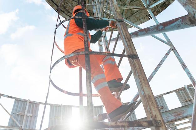 Full shot man met veiligheidsuitrusting op ladder