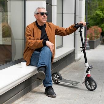 Full shot man zit buiten met scooter