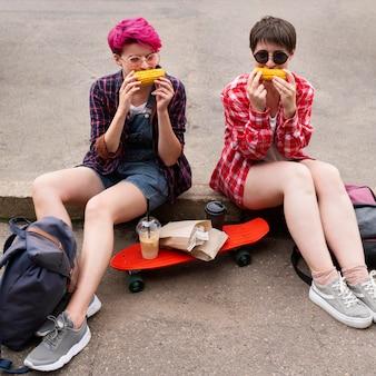 Full shot meisjes samen eten van maïs
