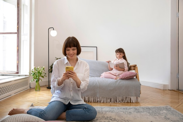 Full shot moeder en meisje in woonkamer