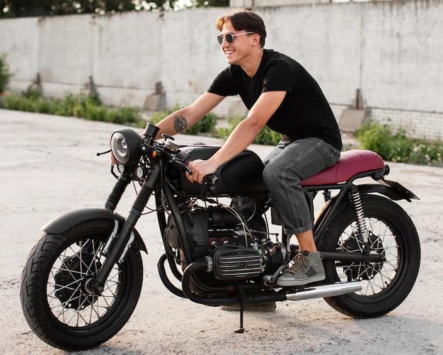Full shot smiley man die zich voordeed op motorfiets