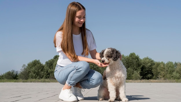 Full shot smiley meisje met hond buitenshuis