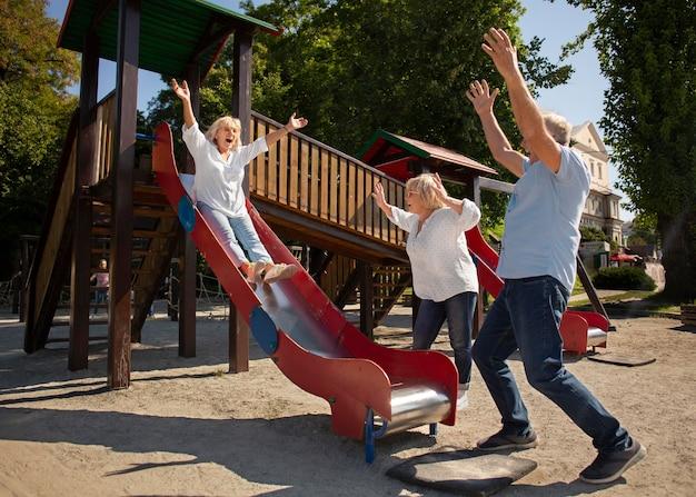 Full shot smiley senior vrouw op slide