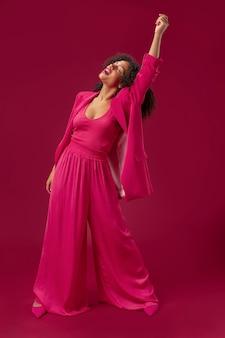 Full shot smiley vrouw poseren met roze outfit