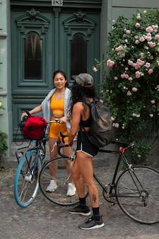 Full shot smiley vrouwen met fietsen