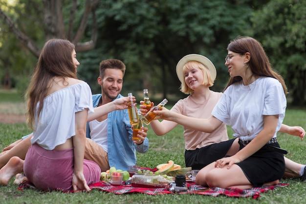 Full shot smileyvrienden die bij picknick roosteren