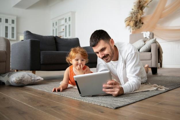 Full shot vader en kind met tablet op de vloer