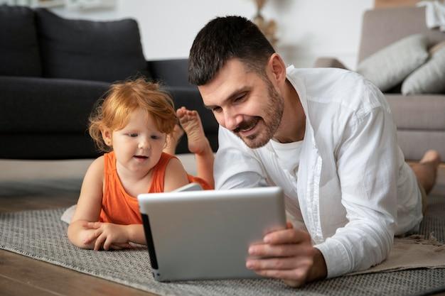 Full shot vader en kind met tablet