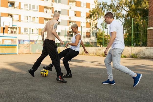 Full shot vrienden die met de bal spelen in de buitenwijken