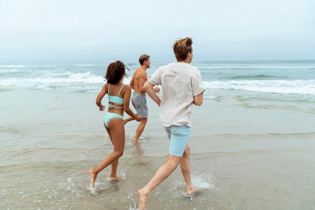 Full shot vrienden die op het strand rennen