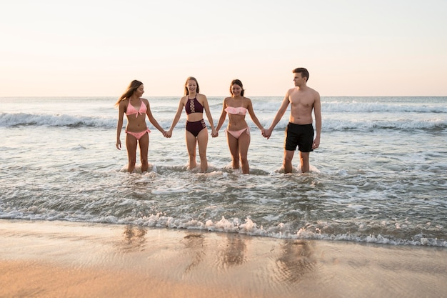 Full shot vrienden hand in hand op strand