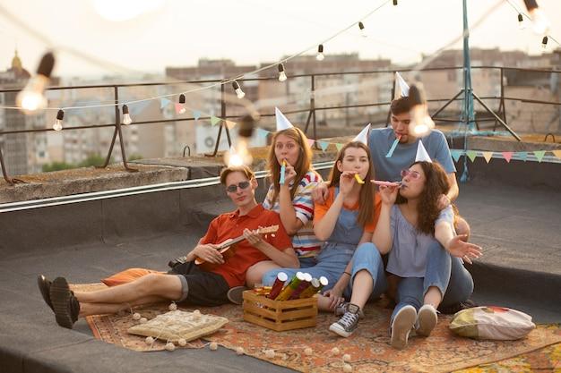 Full shot vrienden op feestje met fluitjes
