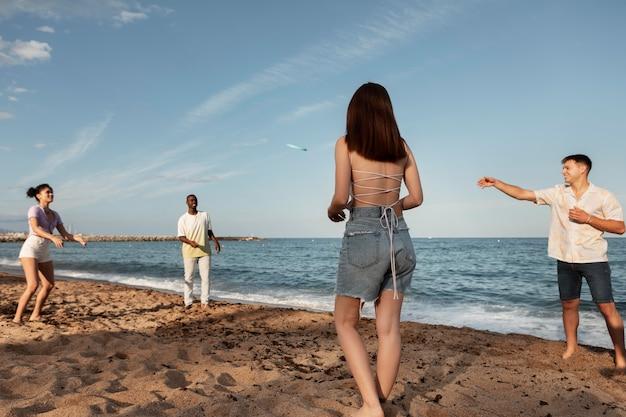 Full shot vrienden spelen met frisbee