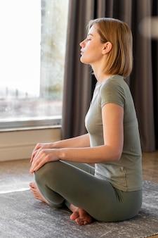 Full shot vrouw mediteren binnenshuis