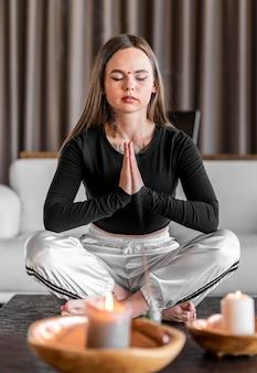 Full shot vrouw mediteren met kaarsen