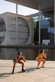 Full shot vrouwen die buiten squats doen