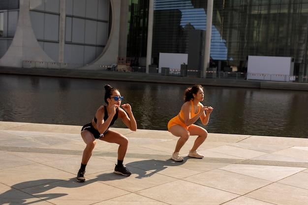 Full shot vrouwen die samen squats doen