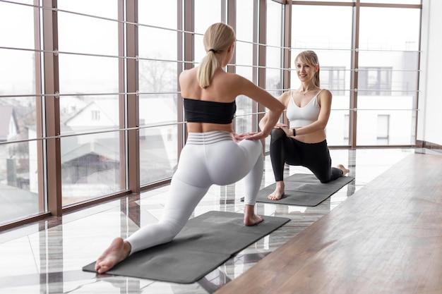 Full shot vrouwen trainen met yogamatten