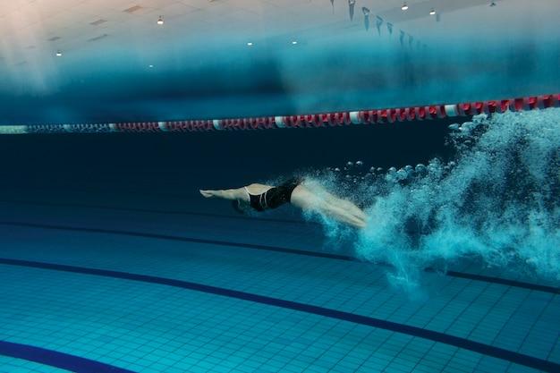 Full shot zwemmer met uitrusting in het zwembad